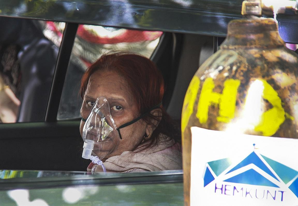 A Covid 19-infected patient uses oxygen provided by an NGO, Hemkunt Foundation, at Sector 42 in Gurugram. (Photo | PTI)