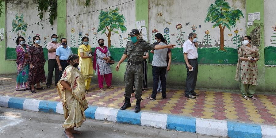 People stand in a queue at a polling station during the 7th phase of West Bengal State Assembly Elections in Kolkata
