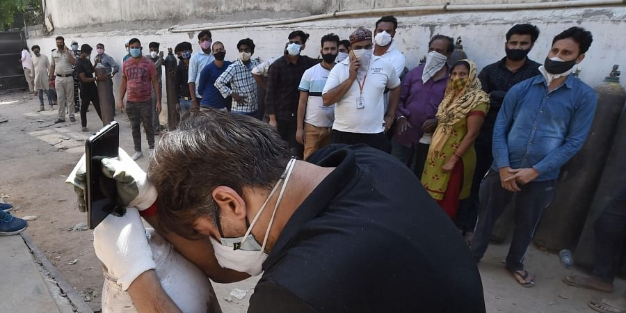 A relatives of a COVID-19 patients along with others waits to refill cylinders with medical oxygen at Badarpur during the second wave of coronavirus pandemic in India, in New Delhi. (Photo   PTI)
