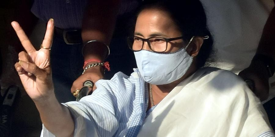 West Bengal CM Mamata Banerjee shows victory signs after cast her vote at a polling station in Kolkata on Monday