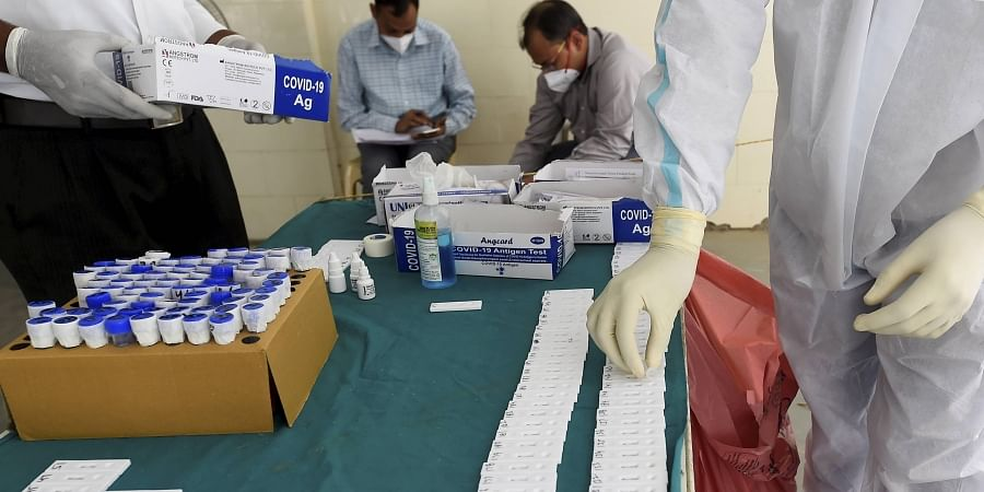 A health worker sorts swab samples at a testing centre, as coronavirus cases surge across the national capital, at MCD dispensary, Mehrauli, in New Delhi.