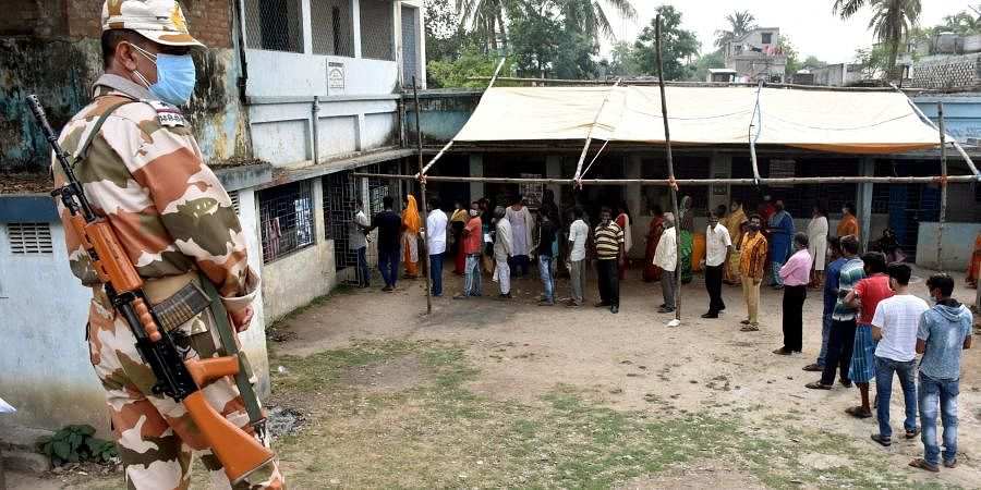 People stand in a queue to cast their votes during the 7th phase of West Bengal Assembly Polls in the Murshidabad district of West Bengal, Monday.