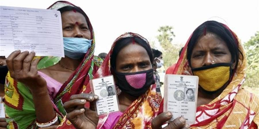 Women show their voter identity cards in West Bengal.