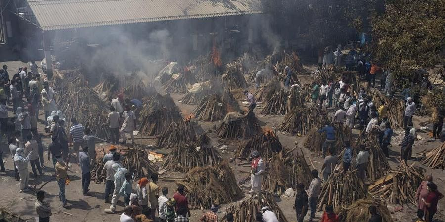 Multiple funeral pyres of those who died of COVID-19 burn at a ground that has been converted into a crematorium for the mass cremation of coronavirus victims, in New Delhi. (Photo   AP)