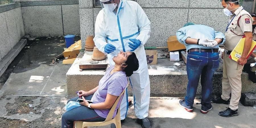 A healthcare worker collects a swab sample on Monday   Shekhar Yadav