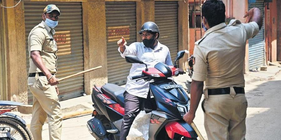 Bengaluru City Police personnel check a motorist during the weekend lockdown, imposed as a measure to contain the spread of Covid-19, in Bengaluru on Sunday. (Photo | Ashishkrishna HP)