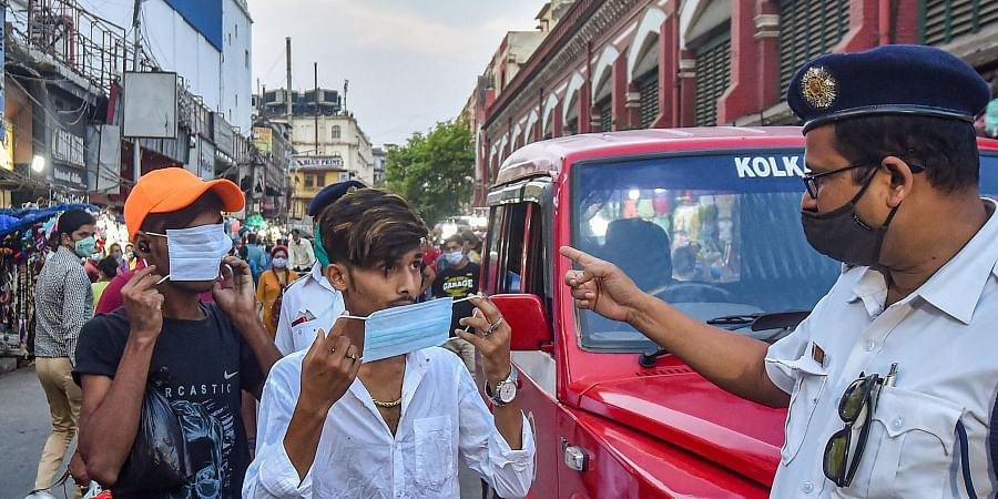 A policeman asks people to wear protective face masks, as coronavirus cases surge across the country, at the New Market area of Kolkata
