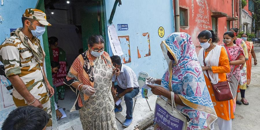 Voters stand in a queue outside a polling station to cast their votes during the last phase of West Bengal Assembly Elections, in Kolkata, Thursday,