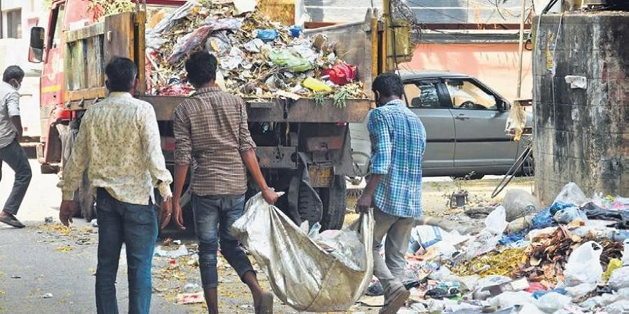 Sanitation workers seen carrying garbage without any protective gear.