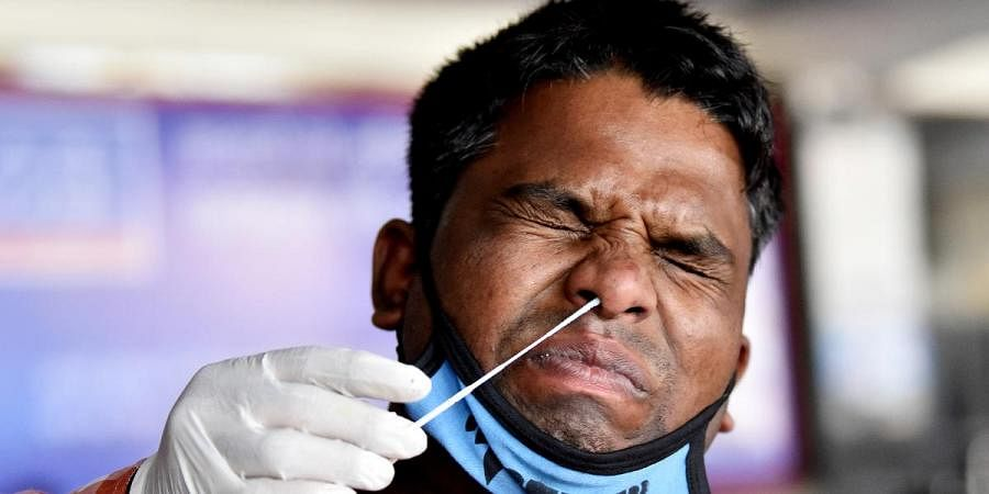 A health worker collects a swab sample of a man for the COVID-19 test at New Delhi railway station