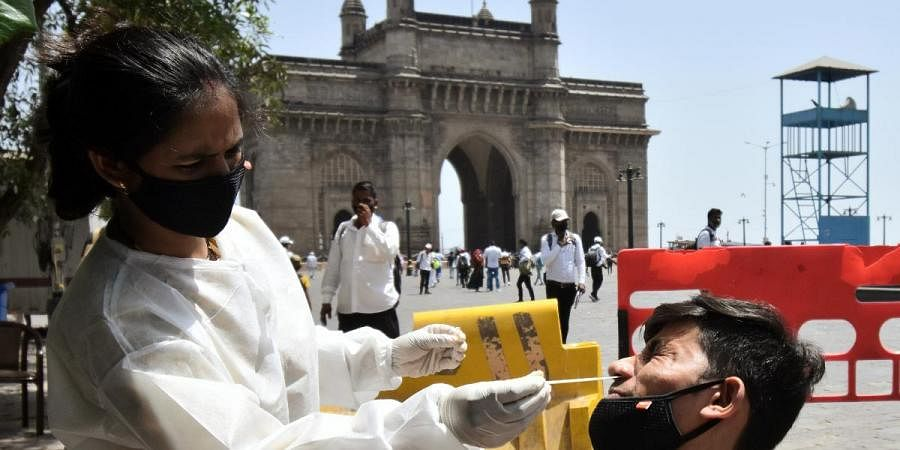 A healthcare worker collects a nasal sample from a man for COVID-19 testing, amid the rise in cases, in Mumbai