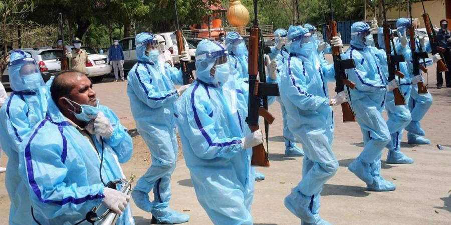 Police personnel protected in PPE kits pay homage to a police inspector who died due to COVID-19 during his last rites in Bhopal
