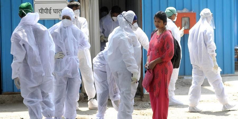 Healthcare workers wear COVID-19 safety kits prior to start their shifts at Jumbo Covid Centre, in Mumbai