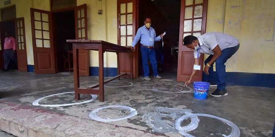 A polling officer draws markers on a floor to ensure social distancing as coronavirus cases spike across the country, on the eve of the second phase of Assam assembly polls, in Nagaon district. (Photo | PTI)