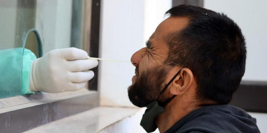 A health worker takes a sample from a man for COVID-19 test in Poonch