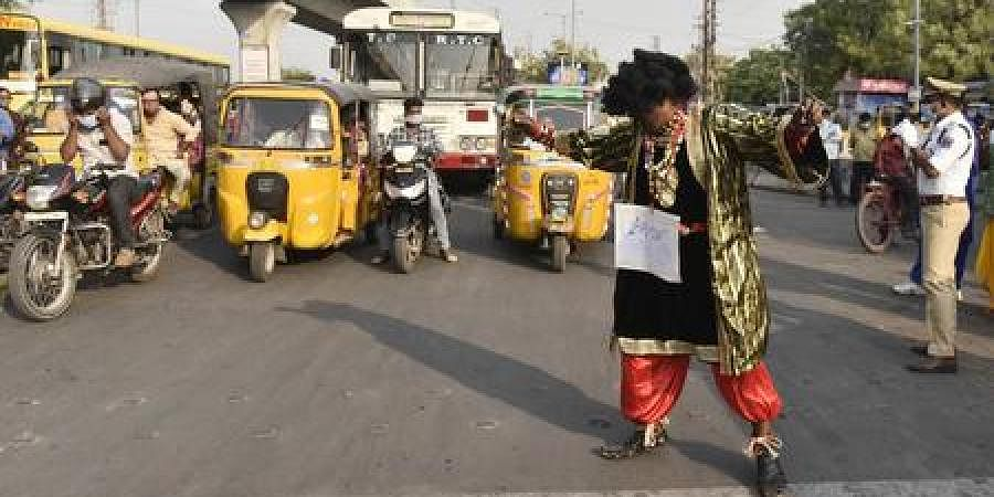 Traffic inspector Anjapalli Nagamallu spreads awareness on COVID-19 at a junction in the city