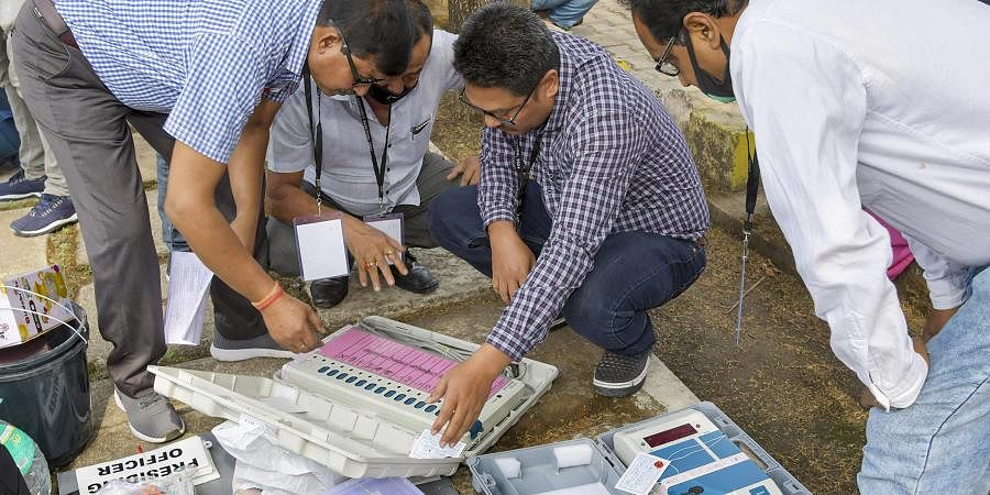 Polling officials check Electronic Voting Machines and other necessary inputs required for the Assembly elections, at a distribution centre, in Kamrup district, Monday