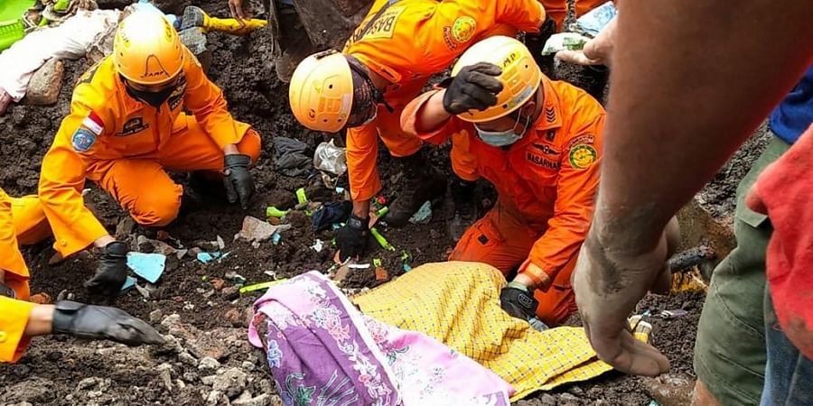 This handout photo taken on April 5, 2021 and released by  BASARNAS shows rescuers retrieving a victim's body in Nelemamadike village, East Flores, in Indonesia.