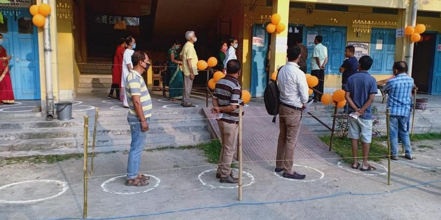 Voters queue up outside a polling station in Assam's Kokrajhar