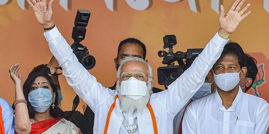 PM Narendra Modi waves at crowd during an election campaign rally in support of BJP candidates at Dumujola Stadium in Howrah district, Tuesday, April 6, 2021.
