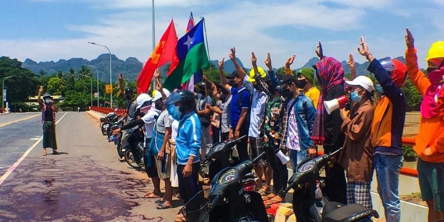 This handout photo from Eindu Youths shows protesters holding up three finger salute in front of red paint splashed on road in Hpa-an township in Myanmar's Karen state.