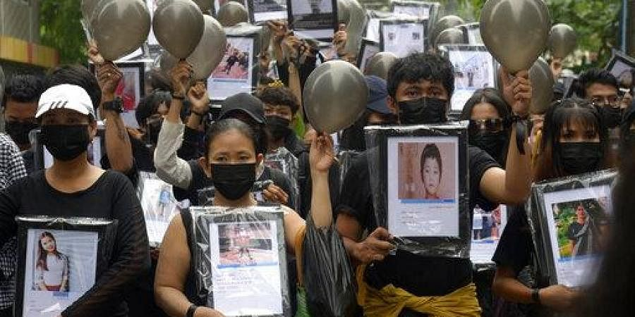 Anti-coup protesters holding pictures of those who died during a protest against the military offer prayers for them, in Yangon, Myanmar