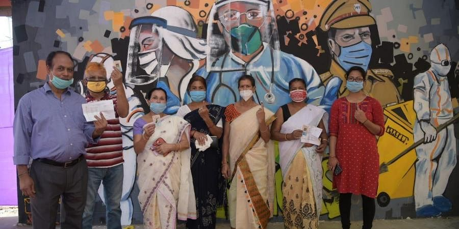 Voters in Assam pose at a polling booth, in front of wall art dedicated to COVID warriors. (Photo | Express)