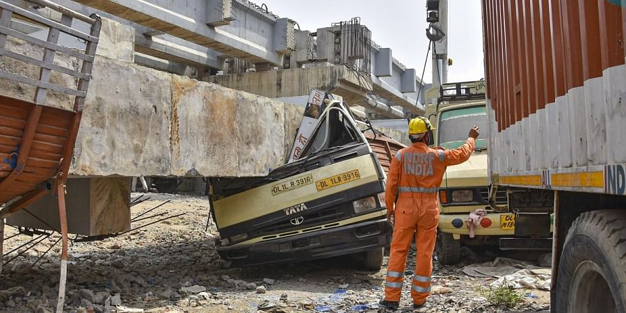 NDRF personnel carry out rescue works after a portion of an under-construction railway bridge collapsed in Rampura area of New Delhi. (Photo | PTI)