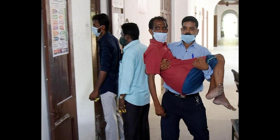 A man carrying a physically challenged person to cast his vote at Lady Wellington School, Triplicane, in Chennai. (Photo   R Satish Babu, EPS)