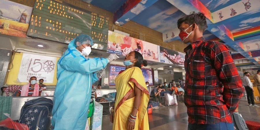 A health worker takes sample from a women for COVID-19 test, as coronavirus cases surge across the country, at New Delhi Railway Station in New Delhi. (Photo | Shekhar Yadav)