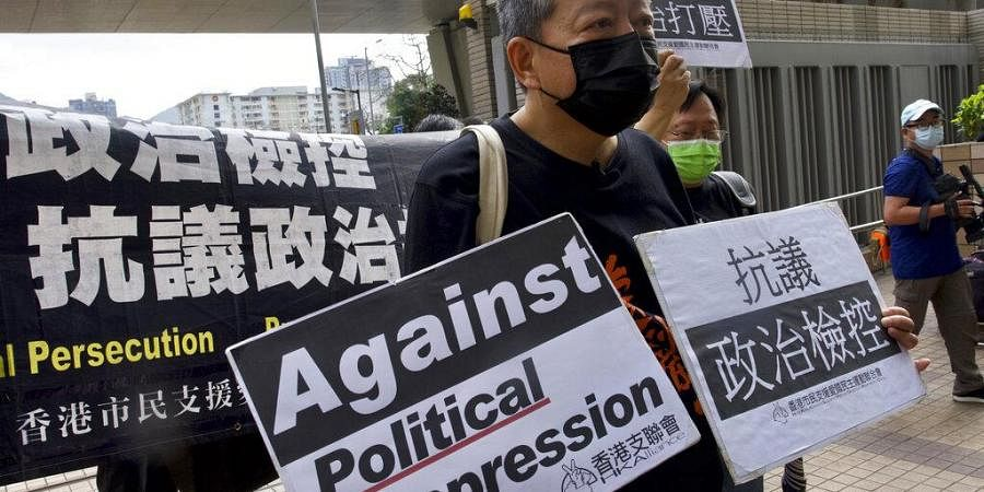Pro-democracy activist Lee Cheuk-yan, center, holds placards as he arrives at a court in Hong Kong