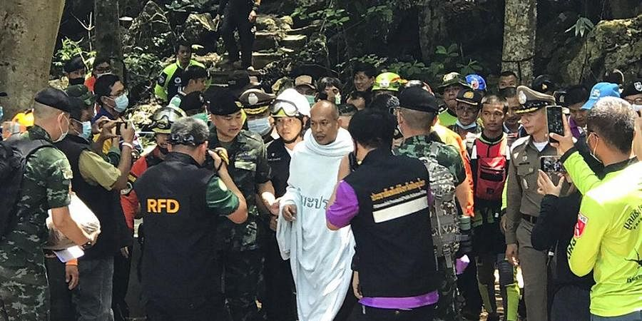 Rescuers help Phra Manas, center, walk out from the Tham Phra Sai Ngam cave in northern Thailand's Phitsanulok province