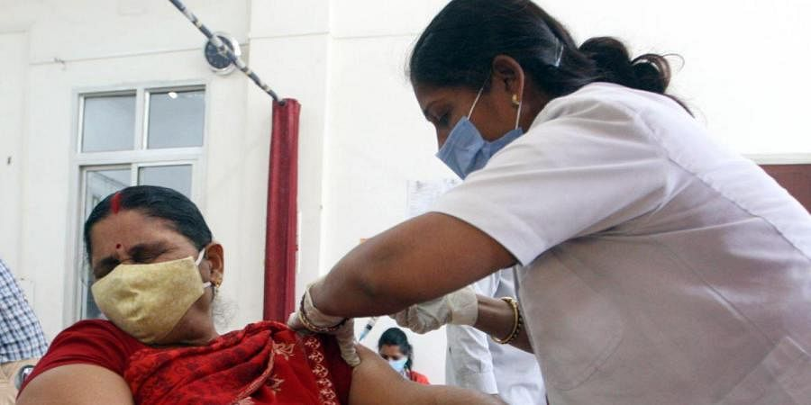 A woman receives a dose of Covishield, a coronavirus disease vaccine, in Prayagraj on Tuesday. (Photo | ANI)