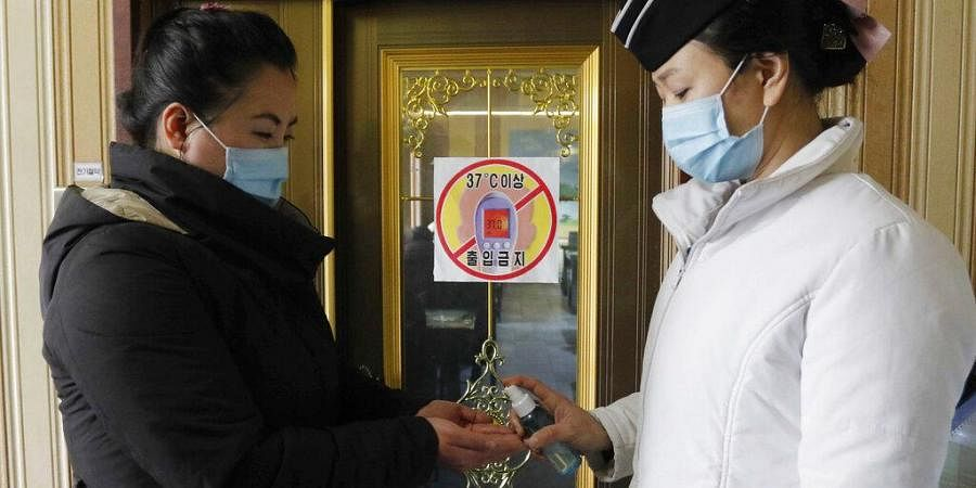 In this Feb. 5, 2021, file photo, a staff member, right, of the Pongnam Noodle House disinfects the hands of a woman coming into its restaurant in Pyongyang, North Korea.