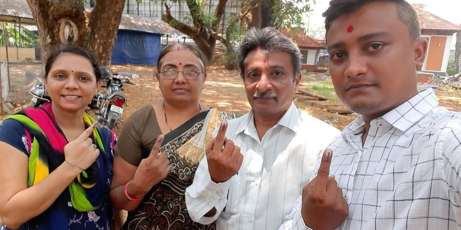 Non-Malayali voters show the ink on their fingers outside a polling station.