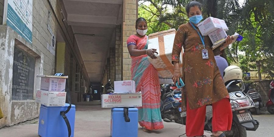 Heath workers bring in boxes of Covid vaccines at Dasappa Hospital in Bengaluru on Tuesday | Vinod Kumar T