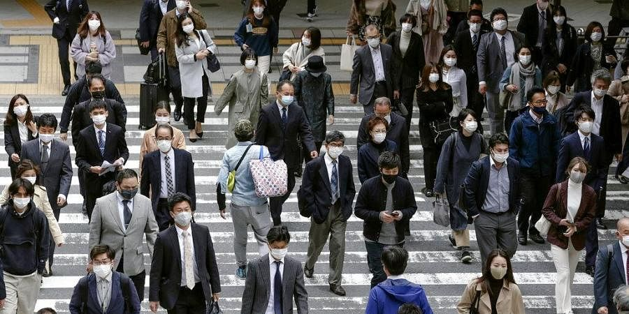 People wearing face masks to help curb the spread of the coronavirus walk in front of Osaka train station