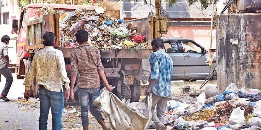 GHMC sanitation workers pick up garbage without safety gear in Hyderabad.