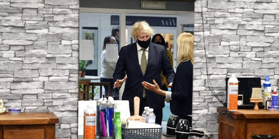 UK Prime Minister Boris Johnson in Lemonheads Barber shop during a visit to Lemon Street Market in Truro, England, Wednesday, April 7, 2021. (Photo | AP)