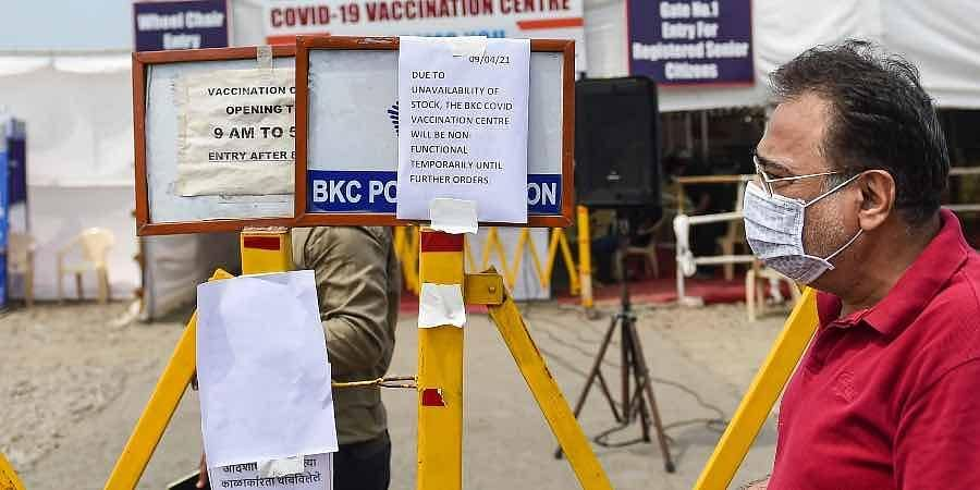 A man walks near a barrier put up outside a Covid-19 vaccination centre as vaccination was stopped due to shortage of vaccine supplies, in Mumbai