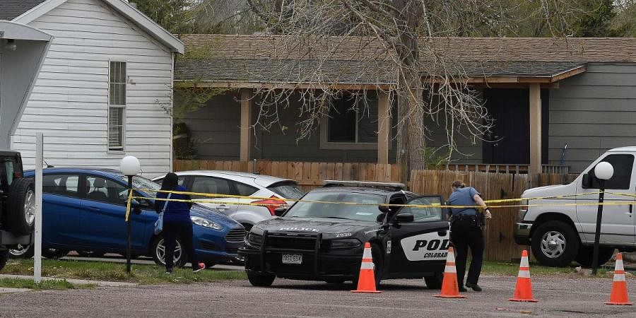 A police officer goes to help a person who was in a different mobile home to be able to get to her car from behind the crime tape in Colorado Springs