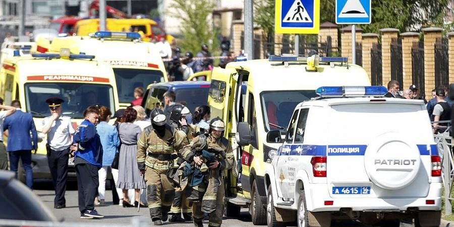 Firefighters walk past ambulances and police cars and a truck parked at a school after a shooting in Kazan, Russia, Tuesday, May 11, 2021.