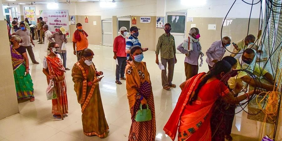 Beneficiares stand in a queue to take COVID-19 vaccine dose, at a vaccination centre in Varanasi