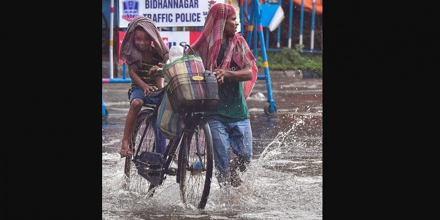 People wade through a water logged road, after heavy rain in Kolkata, Tuesday, May 11, 2021. (Photo | PTI)