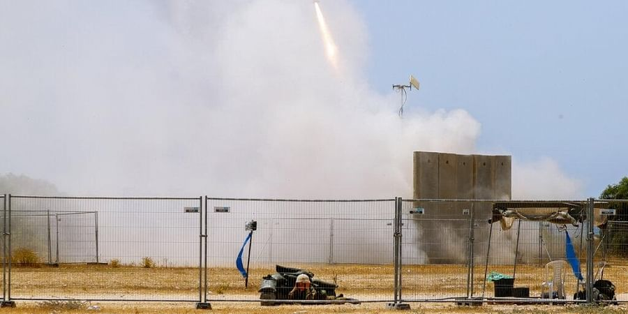An Israeli soldier takes cover as an Iron Dome air defense system launches to intercept a rocket from the Gaza Strip, in Ashkelon, southern Israel, Tuesday, May 11, 2021. (Photo | AP)