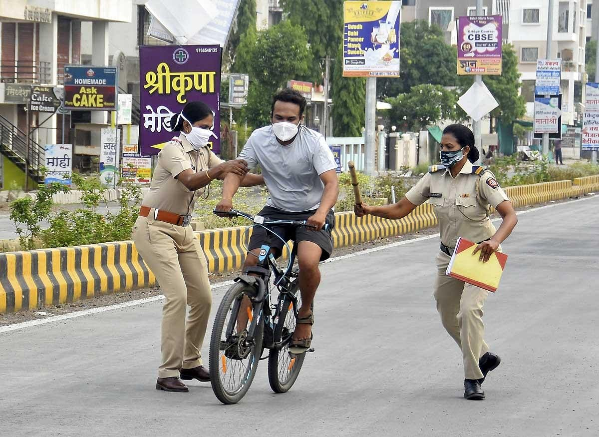 Policewomen attempting to stop a lockdown violator at Amravati in Maharashtra on Tuesday. (Photo | PTI)
