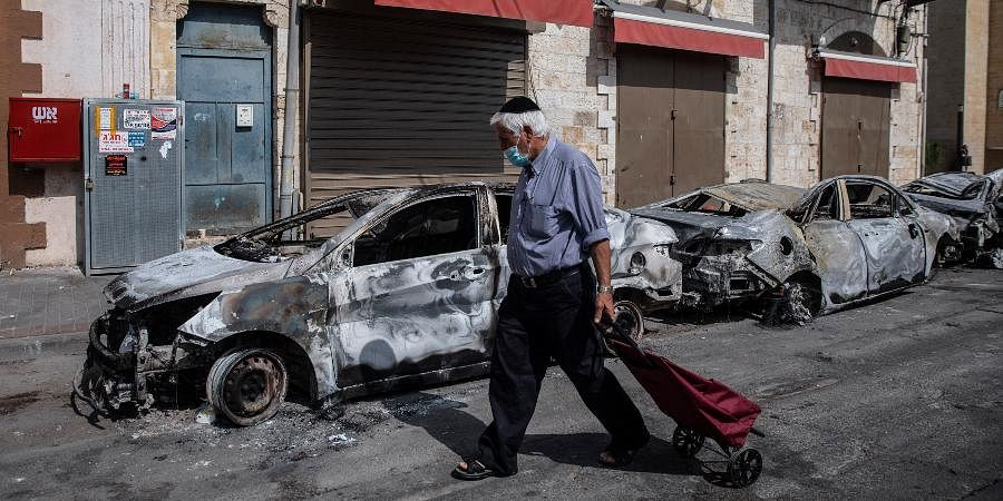 A man passes by cars torched after a night of violence between Israeli Arab protesters and Israeli police in the mixed Arab-Jewish town of Lod, central Israel.