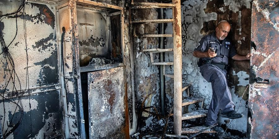 Avi Korkas, a municipality worker, examines the damages of a municipality office in charge of an outdoor food market, that was torched after a night of violence between Israeli Arab protesters and Israeli police.