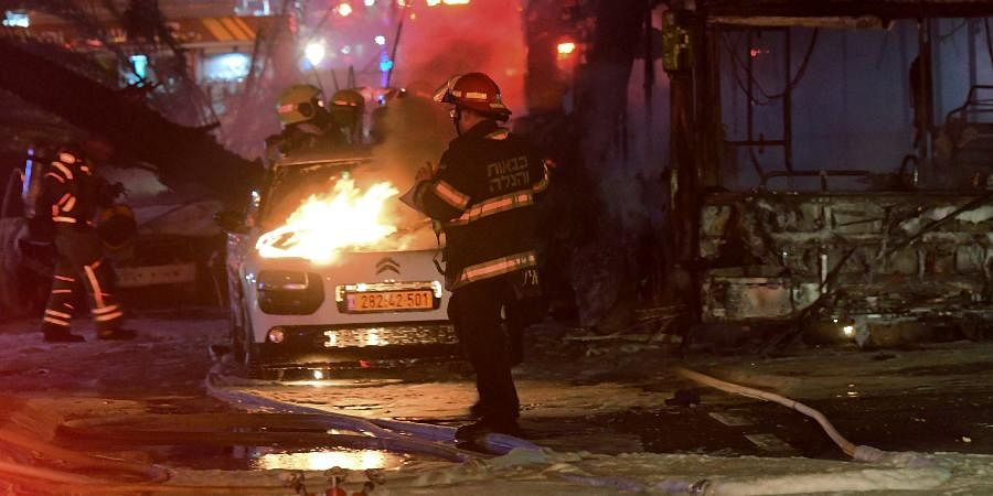 An Israeli firefighter extinguishes a burning car after it was hit by a rocket fired from the Gaza Strip, at the central Israeli town of Holon, near Tel Aviv.