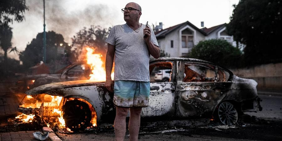 Jacob Simona stands by his burning car during clashes with Israeli Arabs and police in the Israeli mixed city of Lod, Israel.